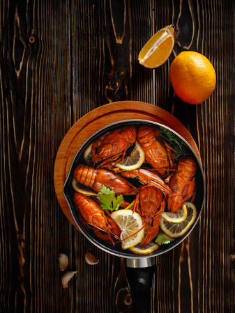 A pan with boiled crayfish stands on a textured brown wooden table top. View from above. Also on the table lie a lemon and garlic.