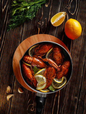 A pan with boiled crayfish stands on a textured brown wooden table top. View from above. Also on the table lie a lemon, garlic, dill greens and parsley.