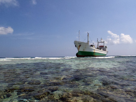 grounded: Ship grounded on a Reef Stock Photo
