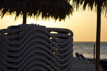Stacked sunbeds on a beach in sunset time Standard-Bild