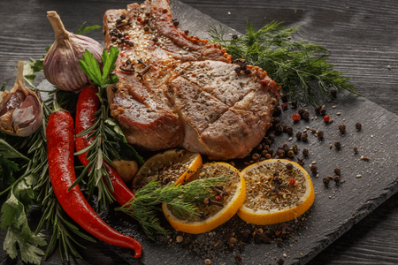 Grilled meat and vegetables on a black rustic background.