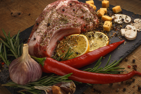 Fresh meat with ingredients for cooking on wood background.