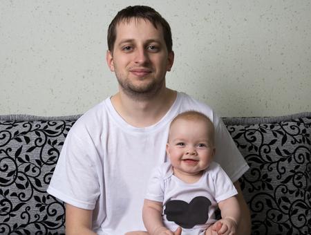 il padre tiene il bambino tra le braccia, il bambino ride sinceramente