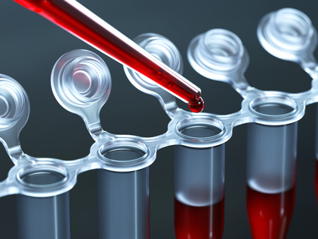 Dropping blood sample in test-tube close-up photo