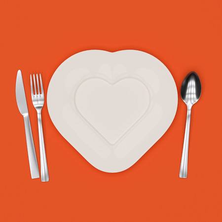 Heart-shaped plate with fork, knife and spoon photo