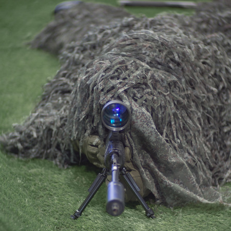 Sniper soldier in ghillie suit aiming with precision rifle
