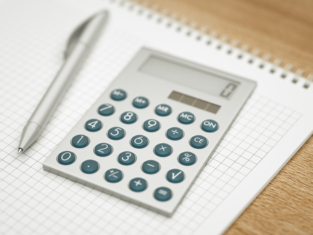 Calculator and pen on squared paper notepad close-up photo