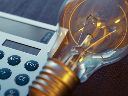 Incandescent light bulb and calculator close-up