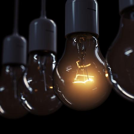 Glowing light bulb illuminating other ones on black background