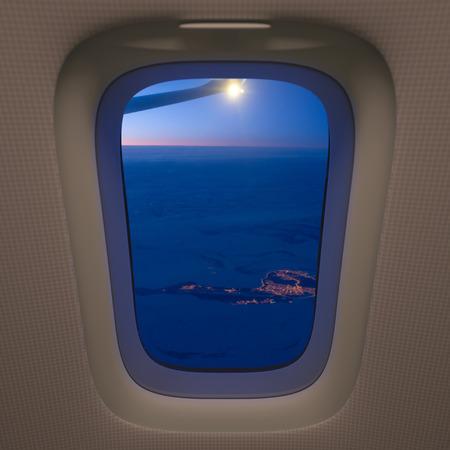 ventana abierta interior: ciudad solitario en los campos de nieve, vista desde la ventana del avión