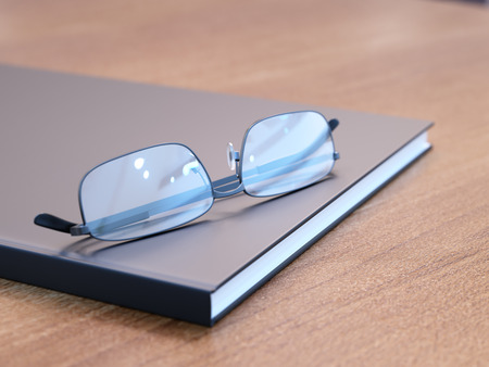 book reviews: Black book with glasses on wooden table close-up Stock Photo