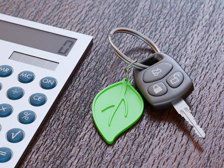 green concept: Car loan calculation concept with car keys and green leaf keychain