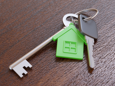 keychain: Green house keychain and house keys on wooden table close-up Stock Photo