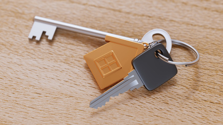gold house: Gold house keychain and house keys on wooden table close-up