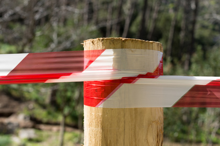 Warning tape attached to a wooden pole and used as a parapet photo