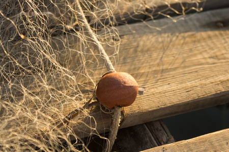 Fishing net with floats resting on wooden jetty photo