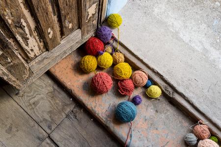 Balls of colored wool in the doorway of an old door photo