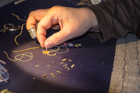 article of clothing: a woman embroiders using the golden thread