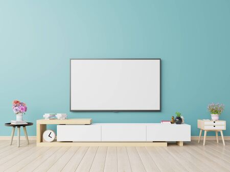 TV on the cabinet in modern living room have plants and book on blue wall background,3d rendering Stock Photo