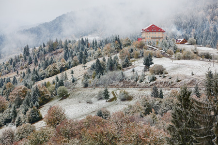 hotel: Hotel in mountains. Snow and fog. Winter coming in Carpathians.