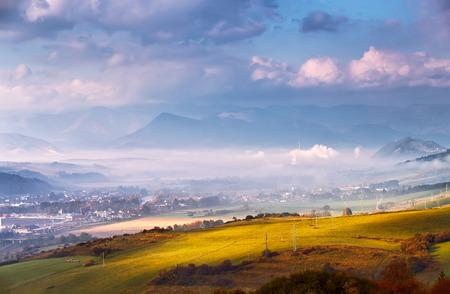 Foggy sunny morning in mountain village. Misty hills in Slova Tatras mountains. Town in valley. Reklamní fotografie - 69448087