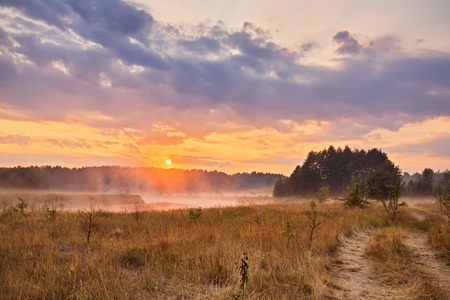 Misty summer sunrise. Foggy river in the morning. Colorful summer morning. Dirt road at summer morning riverbank