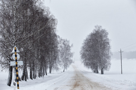 Snowfall and sleet on winter road. Ice snowy road. Winter snowstorm. Black ice and blizzard.