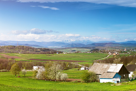 Spring fields and orchard blossom on foothills. Sunny green spring landscape. Spring fields and blooming trees. Village and town behind foothills Stock Photo