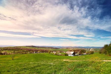Sunny spring day in village and town on foothills. Mountains on background. Sunny green spring landscape. Stock Photo