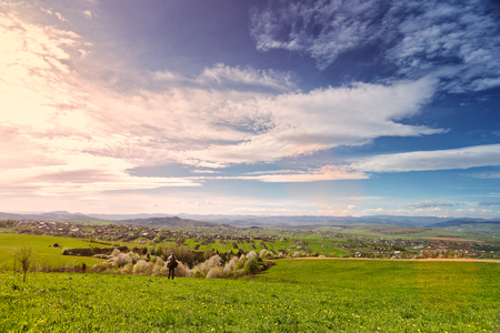 Traveler on green spring meadow. Village on sunny green spring foothills. Orchard blooming on hills. Sunny green blooming spring landscape. Stock Photo