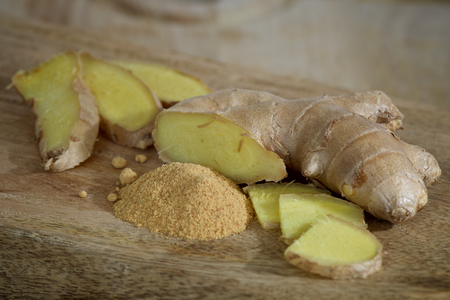 Fresh and Powdered Ginger on a Wooden Plate Close-up