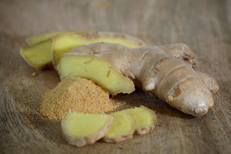 Fresh Sliced and Powdered Ginger on a Wooden Plate Close-up Stock Photo