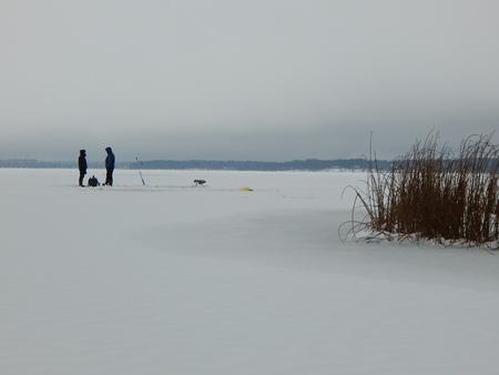 frozen lake: Fishmen on frozen lake Stock Photo