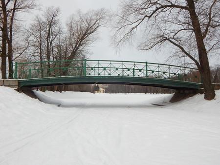 bridgework: Green bridge above pond in winter park Stock Photo