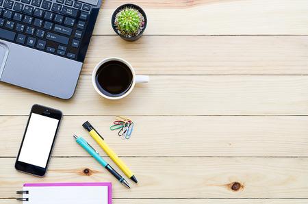 mesa de escritorio de oficina con el ordenador portátil, teléfono inteligente, la taza de café, pluma, lápiz y vista notebook.Top con espacio de copia Foto de archivo