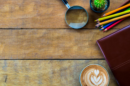 color pencil: Office workspace with leather notebook, magnifying glass, coffee cup  and color pencil .Top view with copy space Stock Photo