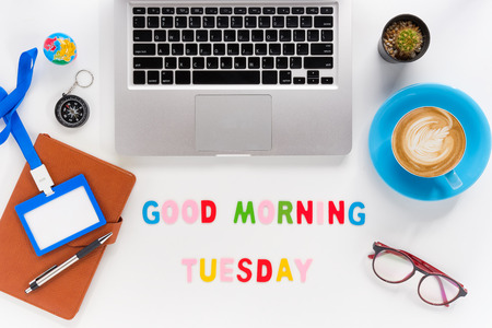 Caption word  Good morning tuesday. White office desk with laptop, diary, eyeglasses, compass, pen, blank identification card and cup of coffee on white background. Stock Photo