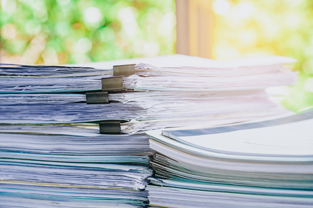 registros contables: Stack of business report paper file on modern white office desk with bokeh background. Foto de archivo
