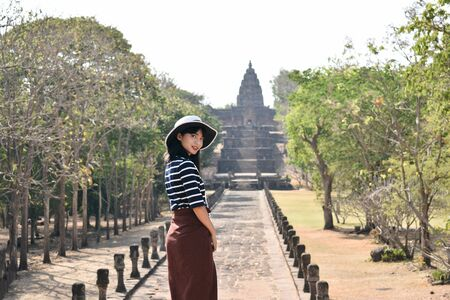Young asian woman in white hat and striped shirt is exploring the ancient ruins of Prasat Hin Phanom Rung temple in Buriram, Thailand.