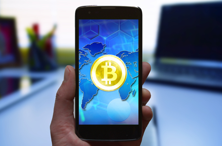 Bitcoin at mobile phone in hand