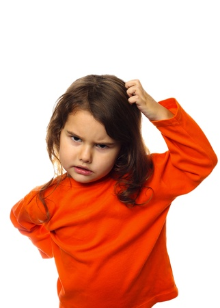 Brunette kid in orange sweater, scratching his head thinking, isolated on white background