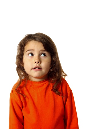 curly brunette baby girl in an orange sweater looks up startled expects nightmare isolated