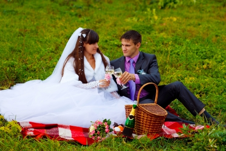 bride and groom at wedding in green field sitting on picnic, drink wine from wine glasses at wedding photo