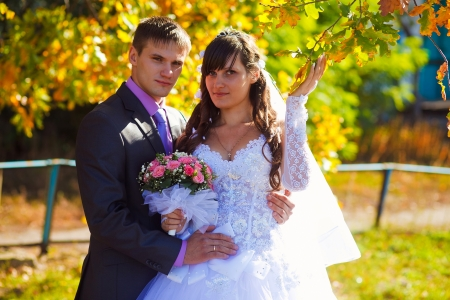bride and groom newlyweds standing next to a tree in autumn with yellow leaves photo