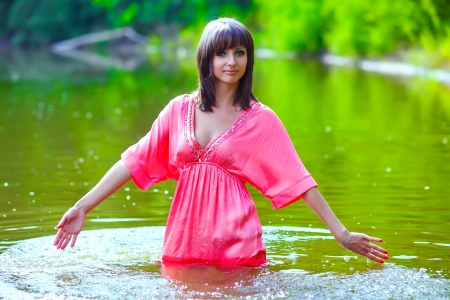 brunette woman model red dress is wet to waist in water touches hand of river photo