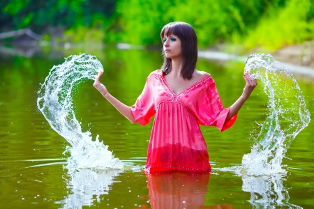 brunette woman red dress is wet to waist in splash water touches hand of river