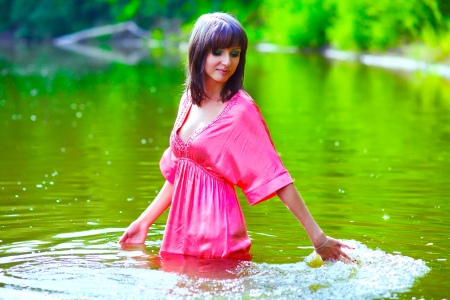 wet clothes: brunette woman red dress is wet to waist in water touches hand of river