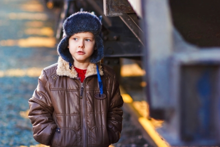 Boy homeless bum on street freezing close to railway carriage in hat and jacket Stock Photo - 16923269