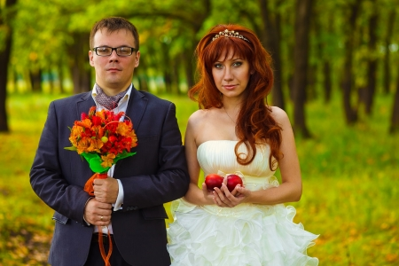 bride and groom standing on a green background in forest, red haired woman holding a bouquet of peach man at wedding photo