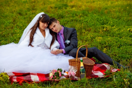 bride and groom wedding in green field sitting on picnic, drink wine from wine glasses at wedding photo